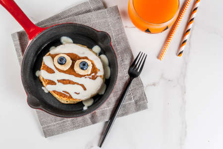 Photo for Funny food for Halloween. Kids breakfast pancake decorated like mummy with white chocolate sauce, banana, berries, with pumpkin smoothie juice, white table copy space top view - Royalty Free Image