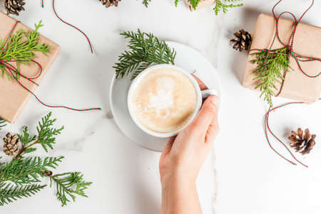 Photo pour Woman hands holding coffee mug, with Christmas gift or present box wrapped in kraft paper, decorated with christmas tree branches, pine cones, red berries, on white marble table, copy space top view - image libre de droit