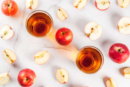 Photo for Fresh organic farm apple juice in glasses with raw whole and sliced red apples, on white marble table, copy space top view - Royalty Free Image
