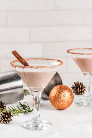 Foto de Ideas and recipes for Christmas drink. Eggnog martini, with cinnamon sticks, on white marble table with Christmas decoration, copy space - Imagen libre de derechos