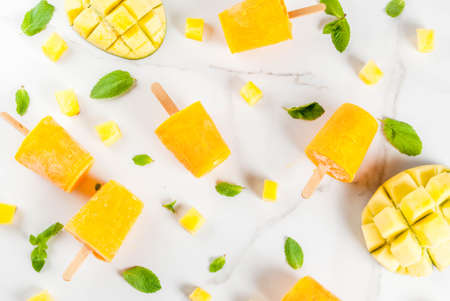 Photo for Ice cream, popsicles. Organic dietary foods, desserts. Frozen mango smoothie, with mint leaves and fresh mango fruit, on a white marble table. Copy space top view - Royalty Free Image