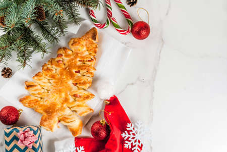 Photo pour Snacks for Christmas party. Closed pizza from puff pastry in the form of a Christmas tree. On a white marble table. With Christmas decorations. top view copy space - image libre de droit