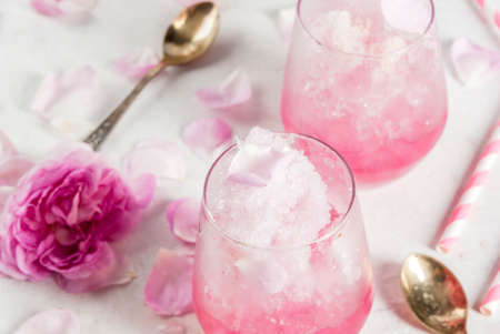 Photo for Summer refreshing desserts. Vegan diet food. Ice cream frozen rose, froze, with rose petals and rose wine. On a white concrete table, with spoons, striped straws, petals and rose flowers. Copy space - Royalty Free Image