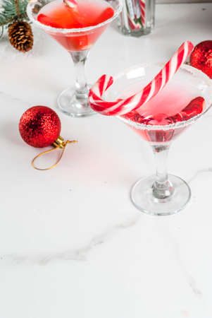 Foto de Christmas drinks, pink peppermint martini cocktail with xmas decoration and candy cane sweet on white marble kitchen table, copy space - Imagen libre de derechos