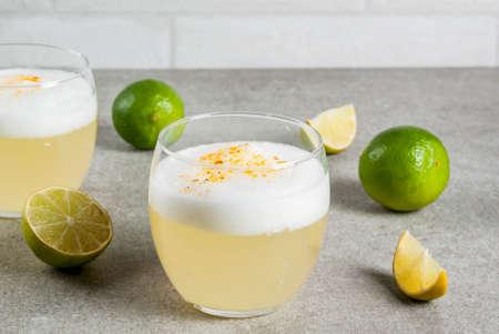 Foto de Peruvian, Mexican, Chilean traditional drink pisco sour liqueur, with fresh lime, on gray stone table, copy space - Imagen libre de derechos