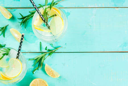 Photo for Cold lemonade or alcohol vodka cocktail with lemon and rosemary, on light blue table, copy space top view - Royalty Free Image