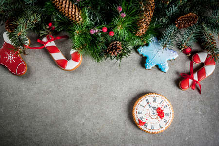 Photo for Christmas background with fir tree branch, homemade colorful gingerbread cookies, pine cones and decorations on grey stone table. Top view, copy space - Royalty Free Image