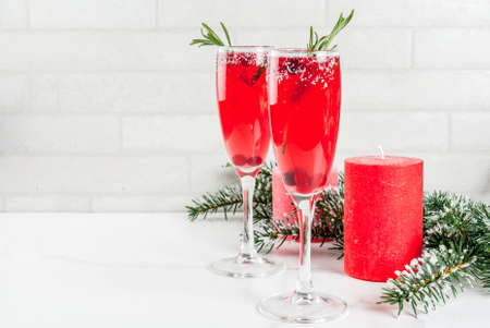 Foto de Christmas morning red cranberry mimosa with rosemary, white marble background copy space with christmas decorations - Imagen libre de derechos