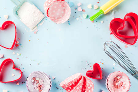 Foto de Sweet baking concept for Valentine's day,  cooking background with baking - with a rolling pin, whisk for whipping, cookie cutters, sugar sprinkling, flour. Light blue background, top view copy space - Imagen libre de derechos