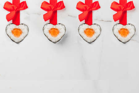 Foto de Real sushi set for valentine's day in form of hearts, with red ribbon and bow. White marble background copy space top view - Imagen libre de derechos