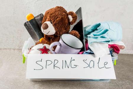Photo pour Plastic spring sale box with toys, clothes gadgets and tools, white grey background copy space - image libre de droit