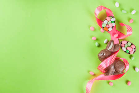 Foto de Easter holiday greeting card background, with chocolate easter bunny, candy eggs, quail eggs and festive ribbon, copy space top view - Imagen libre de derechos