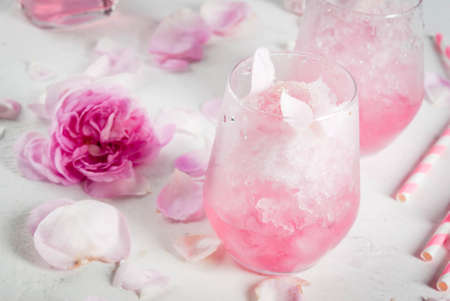 Foto de Summer refreshing desserts. Vegan diet food. Ice cream frozen rose, froze, with rose petals and rose wine. On a white concrete table, with spoons, striped straws, petals and rose flowers. Copy space - Imagen libre de derechos