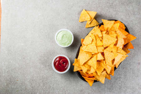 Photo pour Tasty mexican snack,  tortilla chips nachos with ketchup and guacamole, grey stone table, copy space top view - image libre de droit