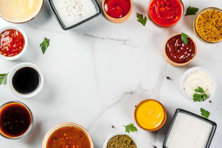 Photo for Set of different sauces - ketchup, mayonnaise, barbecue, soy, teriyaki, mustard, grain hills, pesto, adzhika, chutney, tkemali, pomegranate sauce on white marble background. Top view copy space  - Royalty Free Image