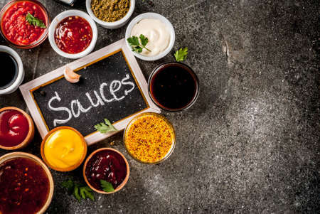 Photo pour Set of different sauces - ketchup, mayonnaise, barbecue, soy, teriyaki, mustard, grain hills, pesto, adzhika, chutney, tkemali, pomegranate sauce on black stone background. Copy space top view - image libre de droit