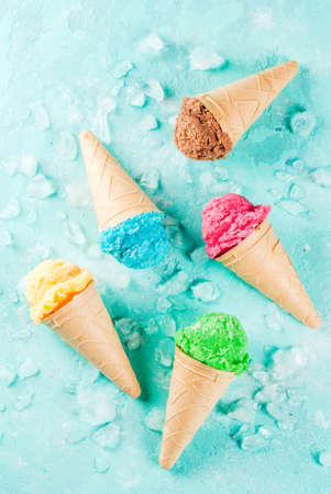 Photo for Selection of various bright multicolored ice-cream in ice cream cones - chocolate vanilla blueberry strawberry pistachio orange, on light blue sunny background, copy space top view - Royalty Free Image