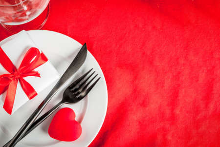 Foto de Valentine's day table setting with plate, fork, knife, gift box and red heart, on red tablecloth background top view copy space - Imagen libre de derechos