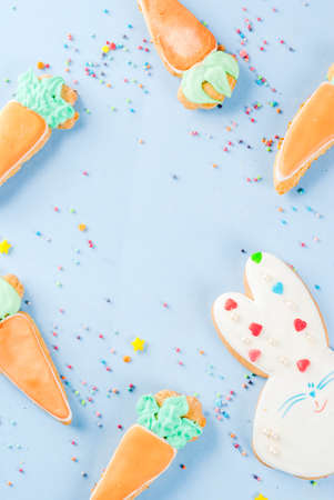 Photo pour Easter holiday concept, sweet cookies in form of carrots, Easter bunny, with sweet sprinkles, light blue background copy space top view, greeting card background - image libre de droit