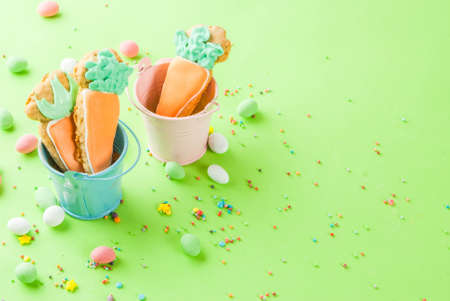 Photo pour Easter holiday concept, sweet cookies in form of carrots,with sweet sprinkles and egg candies,  light green background copy space top view, greeting card background - image libre de droit