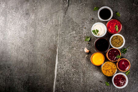 Photo for Set of different sauces - ketchup, mayonnaise, barbecue, soy, teriyaki, mustard, grain hills, pesto, adzhika, chutney, tkemali, pomegranate sauce on black stone background. Copy space top view - Royalty Free Image