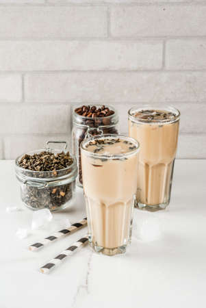 Foto de Asian, Malaysian traditional drink Yuenyeung from tea, coffee, milk, with ice cubes, on white kitchen background copy space - Imagen libre de derechos