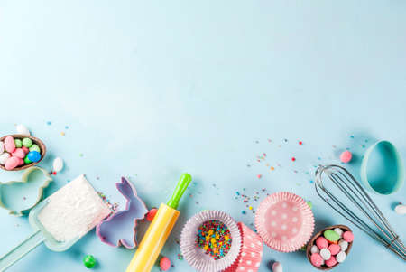 Foto de Sweet baking concept for Easter,  cooking background with baking - with a rolling pin, whisk for whipping, cookie cutters, sugar sprinkling, flour. Light blue background, top view copy space - Imagen libre de derechos