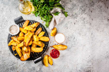 Photo pour baked fried potatoes with garlic, herbs, red and white sauces, on grey stone background copy space top view - image libre de droit