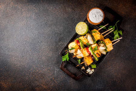 Foto de Vegan diet food, Grilled cheese and vegetables kebab, indian style Paneer Tikka, with white sauce and lime, on dark concrete background, copy space top view - Imagen libre de derechos