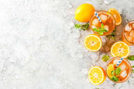 Foto de Cold summer drink. iced tea with lemon and mint, on grey stone background.  Copy space top view - Imagen libre de derechos