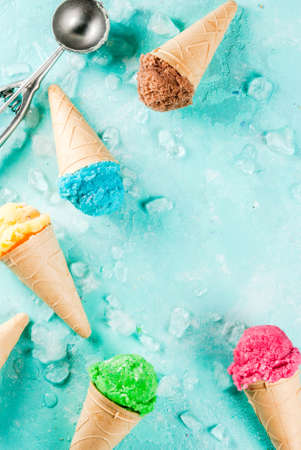 Foto de Selection of various bright multicolored ice-cream in ice cream cones - chocolate vanilla blueberry strawberry pistachio orange, on light blue sunny background, copy space top view - Imagen libre de derechos