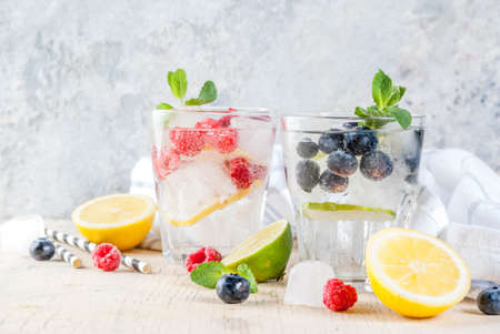 Photo pour Various berry lemonade or mojito cocktails, fresh iced lemon lime raspberry blueberry infused water, summer healthy detox drinks light background copy space - image libre de droit