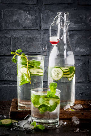 Photo pour Summer fresh iced drink, mint and cucumber infused water, summer healthy detox mojito cocktail, light background copy space - image libre de droit
