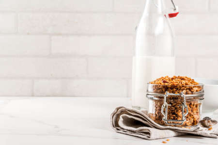 Photo for Homemade granola from mix of cereals (barley, oat, rye, bran) with dry fruits, nuts, with fresh organic milk on white marble background - Royalty Free Image