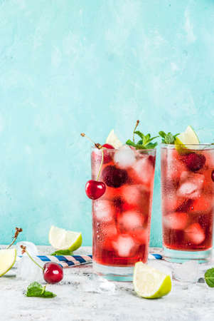 Photo for Summer iced refreshment drink, cherry cola lemonade or mojito cocktail in tall glass, on light blue and grey background copy space - Royalty Free Image