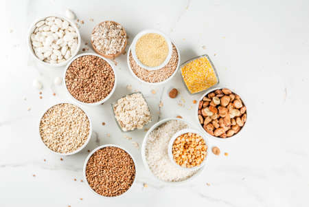 Photo pour Selection various types cereal grains groats  in different bowl on white marble background, copy space top view - image libre de droit