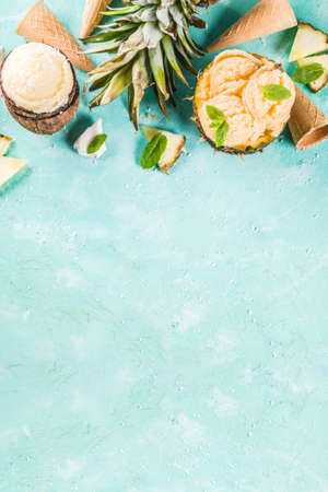 Photo for Summer holiday vacation concept, set various tropical ice cream sorbets, frozen juices in pineapple, grapefruit and coconut, light blue concrete background copy space - Royalty Free Image