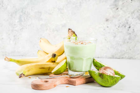 Photo pour Healthy summer drink, avocado and banana smoothie with lime, granola and coconut milk, dark rusty background copy space - image libre de droit
