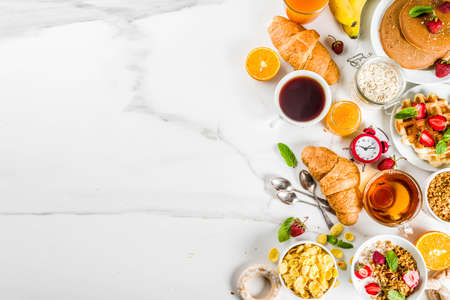 Foto de Healthy breakfast eating concept, various morning food - pancakes, waffles, croissant oatmeal sandwich and granola with yogurt, fruit, berries, coffee, tea, orange juice, white background - Imagen libre de derechos