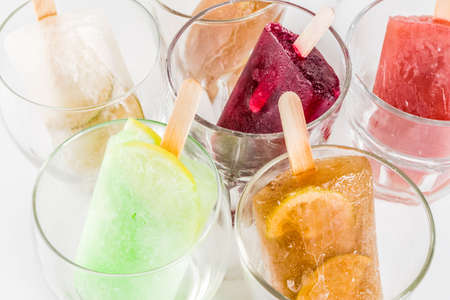 Photo for Summer party food ideas, frozen boozy alcohol cocktails popsicles - Prosecco, Vodka lime mojito, Champagne, Bellini, Margarita, Negroni etc white marble table copy space - Royalty Free Image