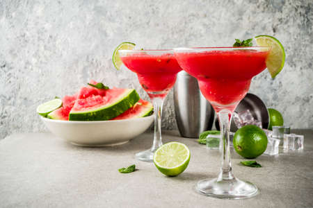 Photo for Watermelon margarita cocktail with lime and sliced watermelon, light concrete background copy space - Royalty Free Image