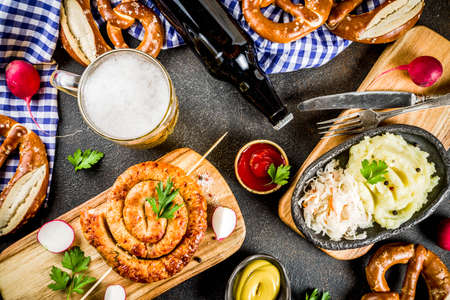 Foto de Oktoberfest food menu, bavarian sausages with pretzels, mashed potato, sauerkraut, beer bottle and mug, dark rusty background copy space top view - Imagen libre de derechos