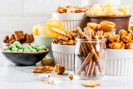 Photo for Variation different unhealthy snacks crackers, sweet salted popcorn, tortillas, nuts, straws, bretsels, white marble background copy space - Royalty Free Image