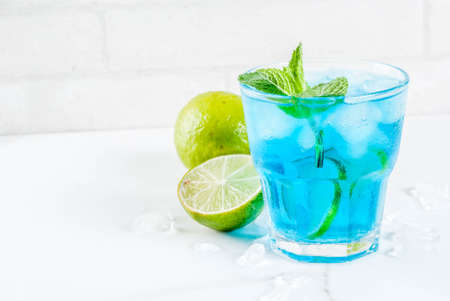 Photo pour Colorful summer beverage, iced blue  alcohol cocktail drink with lime and mint, white marble background copy space - image libre de droit