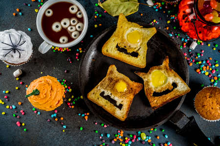Photo pour Funny children's treats for Halloween, an idea for a festive breakfast. Sandwiches toast with eggs, looking like creepy monsters, hot chocolate with marshmallow eyes and funny monster cupcakes. - image libre de droit