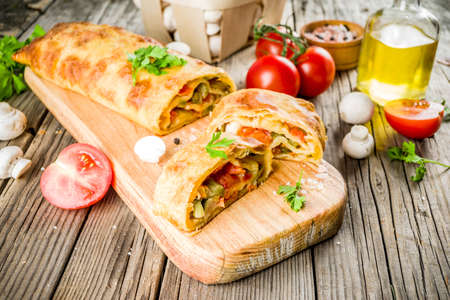 Photo pour Vegetable savory strudel, homemade autumn baking, with tomatoes, bell pepper, mushrooms, wooden background copy space - image libre de droit
