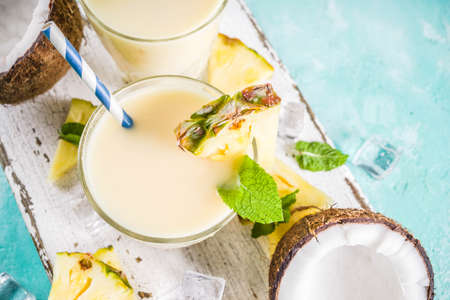 Photo for Refreshing summer drink, homemade pina colada cocktail, on a light blue background, with pieces of pineapple, coconut, ice and mint leaves, copy space top view - Royalty Free Image