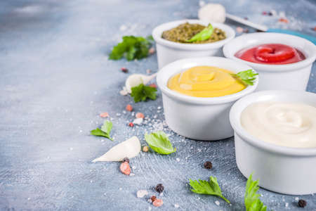 Photo pour Set of four classic sauces - ketchup, mayonnaise, mustard, pesto - with herbs and spices. Blue concrete background top view copy space - image libre de droit