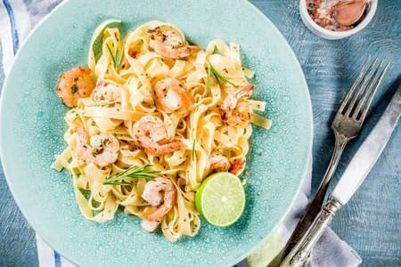 Photo for Italian food, classic fettuccine pasta with shrimp and creamy sauce, olive oil, lime and herbs, light blue table copy space top view - Royalty Free Image