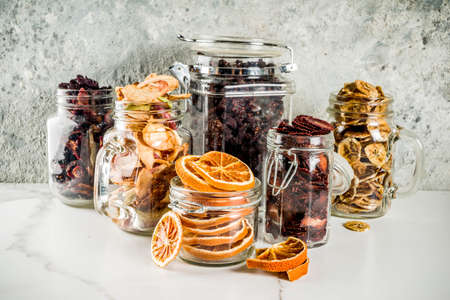 Photo for Home autumn harvest, dried fruits and berries in glass jars for canned preserves, strawberries, raspberries, apples, bananas, oranges, light concrete background, copy space - Royalty Free Image